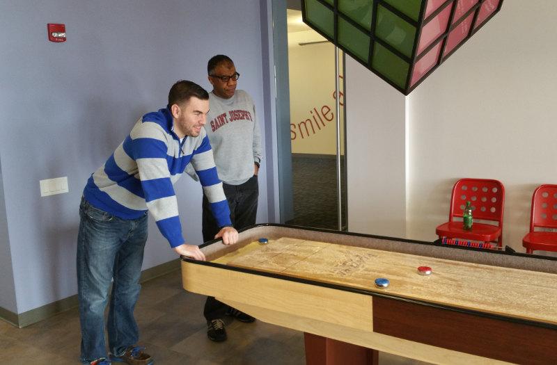 Employees take a break from work to play shufflepuck.
